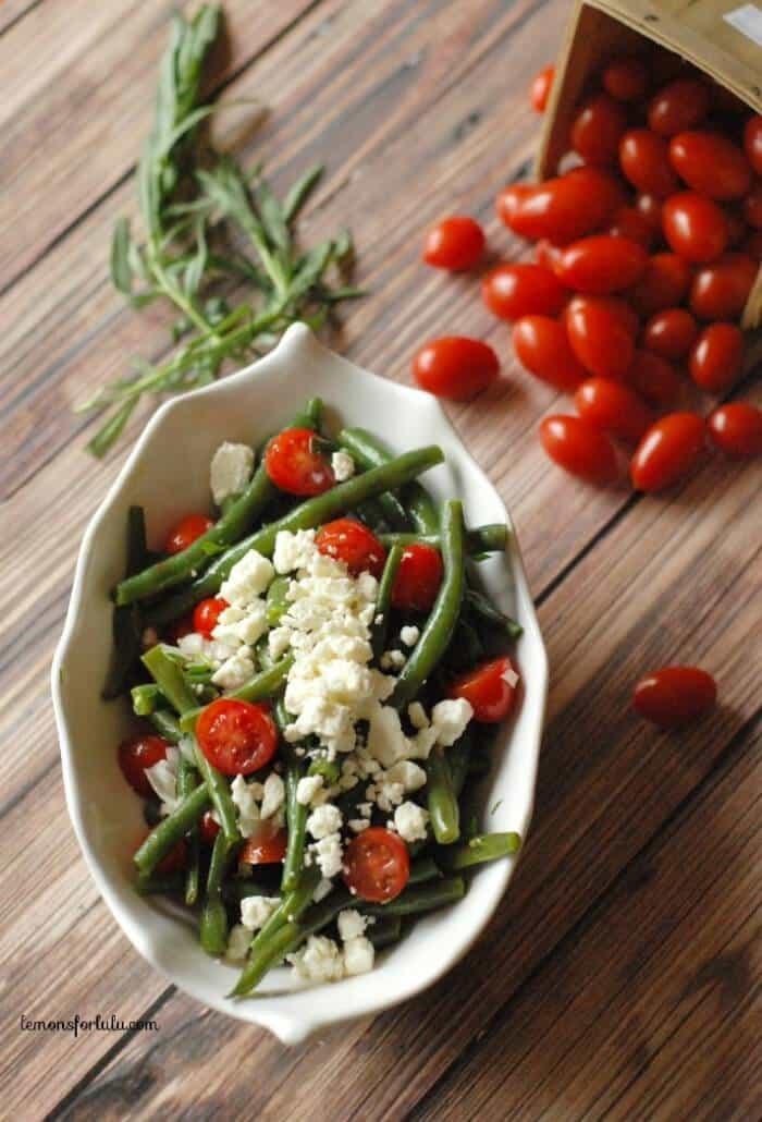A simple green bean salad with cherry tomaotes, feta and a tarragon vinaigrette! www.lemonsforlulu.com