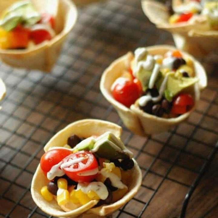 Mini tortilla cups filled with a taco flavored cream cheese, black beand and lots of veggies! www.lemonsforlulu.com