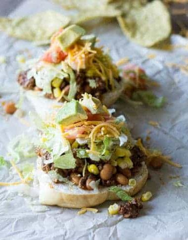 Easy and delicious taco sloppy joes on parchment paper topped with delicious tomatoes, cheese, sweet corn and avocado.