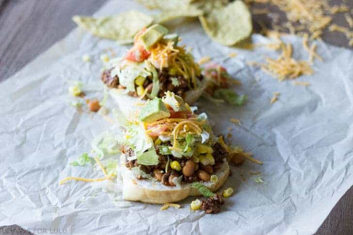 Easy sloppy joes turned into sloppy joe tacos with avocados, cheese, lettuce, tomatoes and corn on parchment papers.