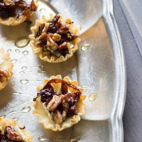 Baked brie cups topped with sweet caramelized onions, spicy nuts and a drizzle of honey! A simple, but pleaseing appetizer! www.lemonsforlulu.com #PantryInsider
