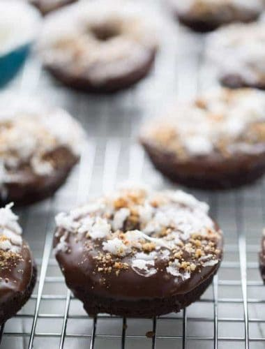 Chocolate donuts are baked in the oven then dipped in a smooth chocolate glaze and covered in coconut and almonds to taste just like the favorite almond coconut candy bar! lemonsforlulu.com
