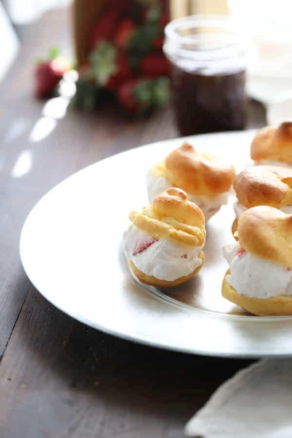 Easy profiterole recipe that is filled with a homemade strawberry and cream filling! So easy and so good! lemonsforlulu.com