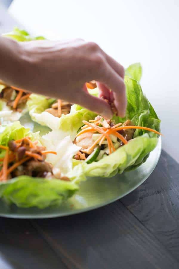 Sriracha spiced almonds make this chicken lettuce wraps recipe really stand out! Chicken, mushrooms, cucumber and carrots make an excellent filling for this Asian inspired meal! lemonsforlulu.com