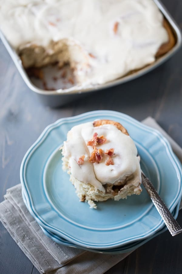 Soft cinnamon rolls are filled with crispy bacon then topped with an easy maple frosting recipe. lemonsforlulu.com