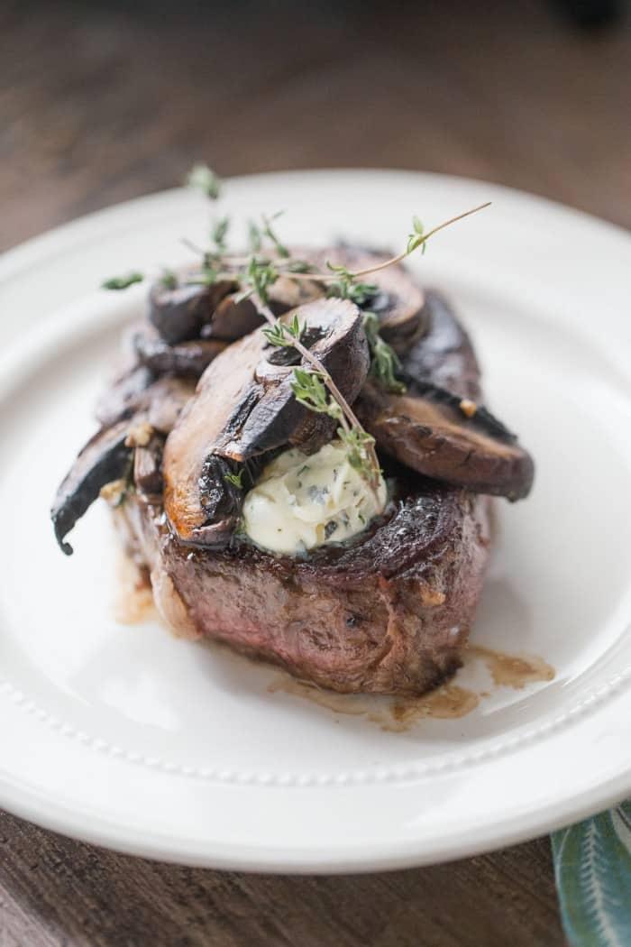 A simply seasoned beef tenderloin recipe with portobello mushrooms and an easy herb butter. lemonsforlulu.com