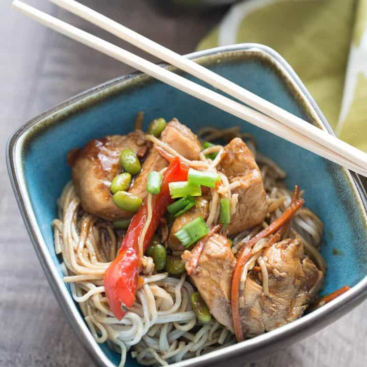 Blue bowl of Chicken Teriyaki with Noodles with wooden chopsticks.