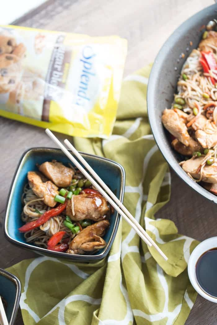 Bag of splenda next to Chicken Teriyaki with veggies in a small blue bowl and wooden chopsticks.