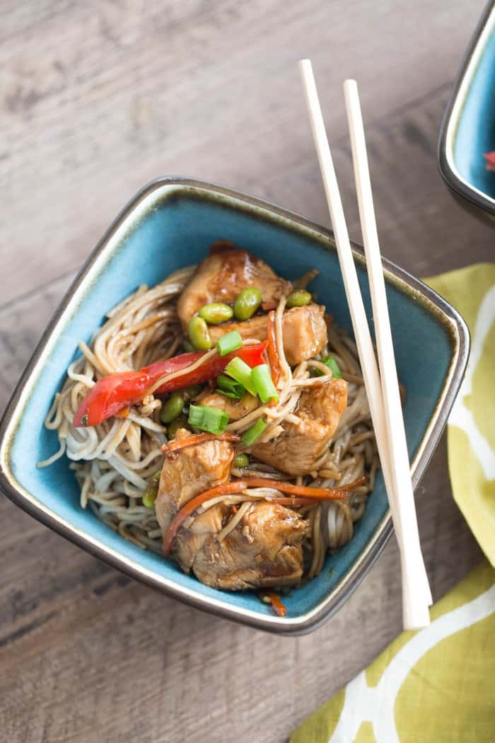 Easy chicken teriyaki recipe with red pepper, carrots, edamame and soba noodles in a small blue bowl with chopsticks on a wooden table.
