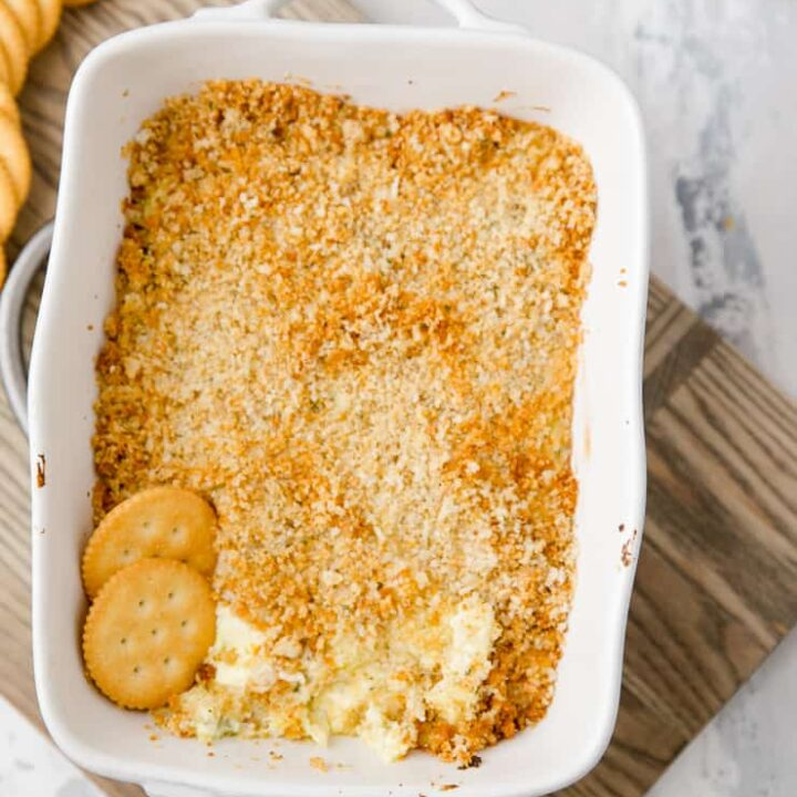 dill pickle dip in a dish with crackers in it
