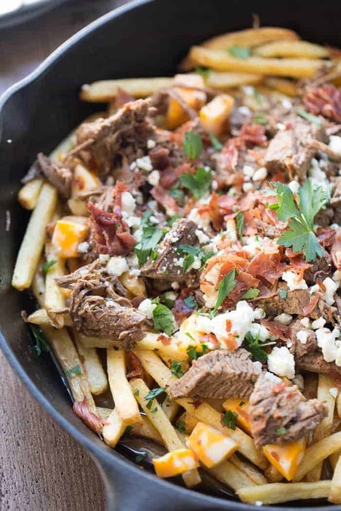 This easy poutine recipe has slow cooked brisket, bacon and two kinds of cheese !