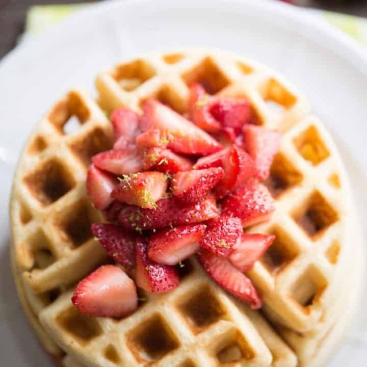 This easy homemade waffles recipe gets a tangy kick from key lime and is served with a sweet strawberry topping.