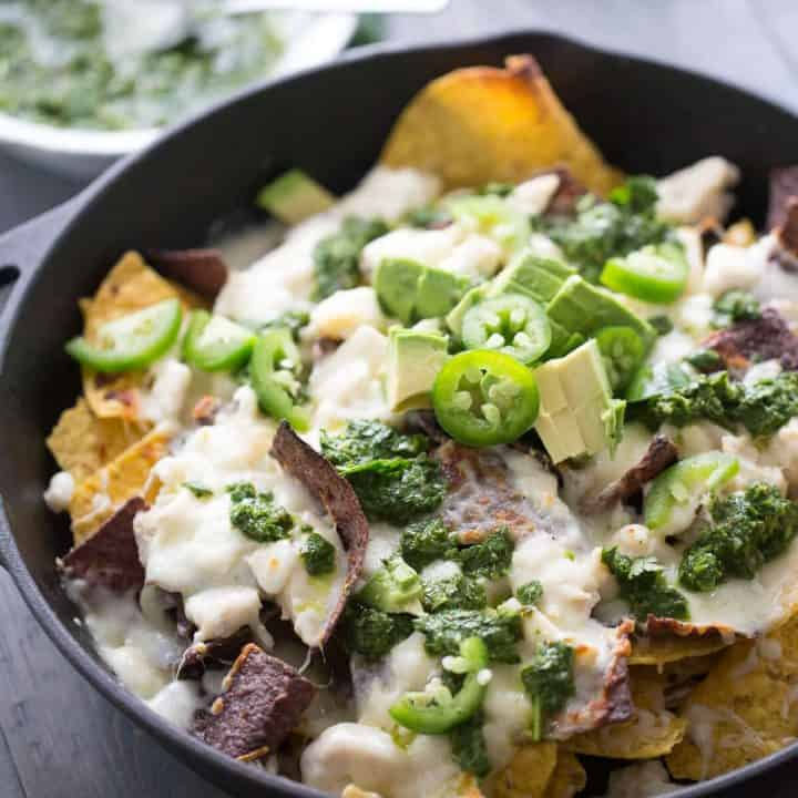 Loaded Nachos Brazilian Style! These nachos are topped with both pork and chicken, lots of cheese, creamy avocados and a homemade chimichurri sauce!