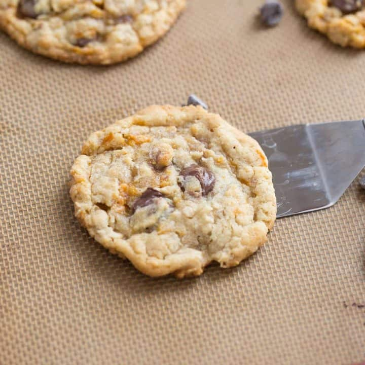 Butterfinger cookies on a baking dish surrounded by big chocolate chips.