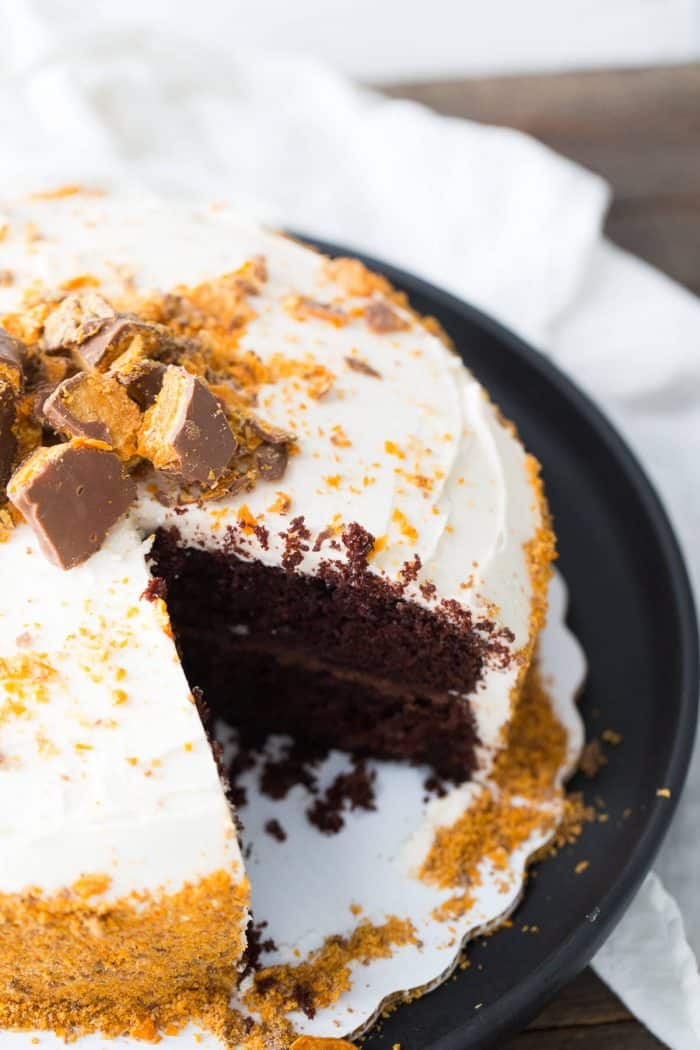 Butterfinger chocolate cake with a piece missing