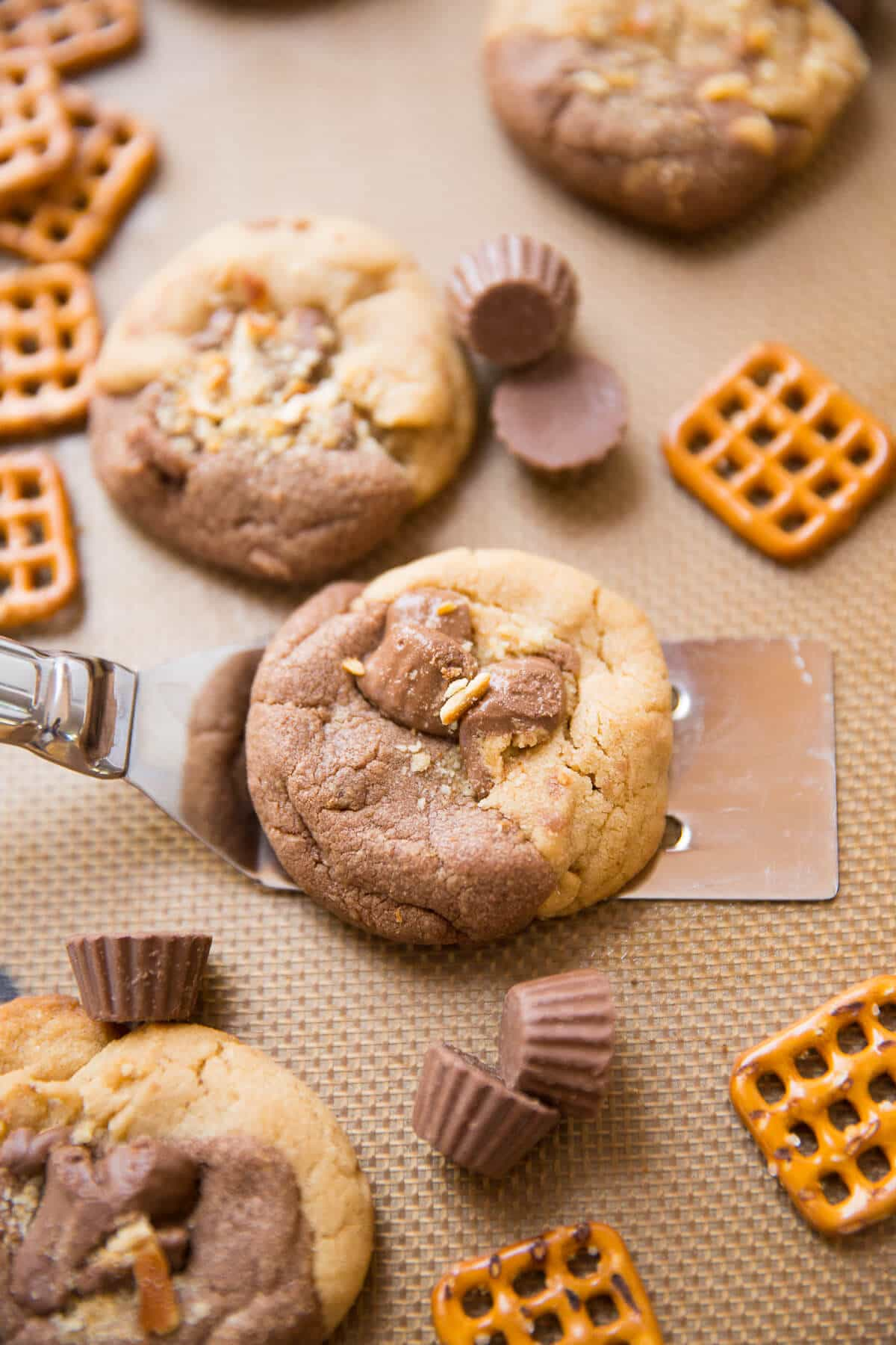 Chocolate and peanut butter are swirled together in these Chocolate Peanut Butter Explosion Cookies! Peanut butter cups, peanut butter chips all make an appearance as do pretzels which add a little saltiness to the sweet mix!