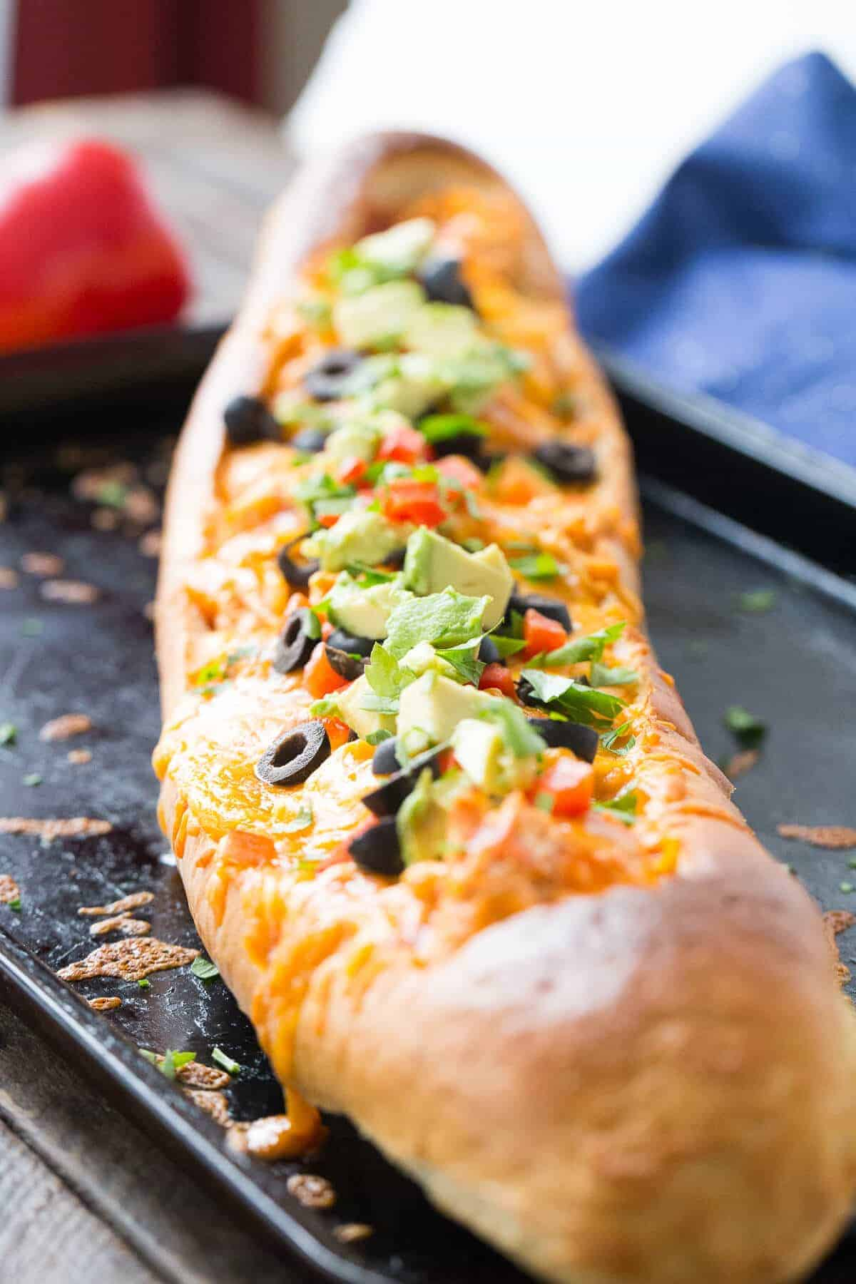 This chicken enchilada bread makes dinner simple! Chicken and sauce are stuffed inside French bread and baked! You decide on the toppings!