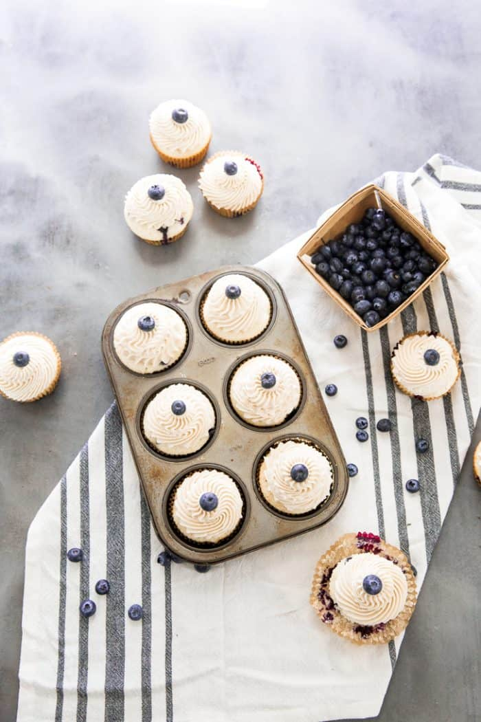 Blueberry cupcakes in a tin with blueberries on the side