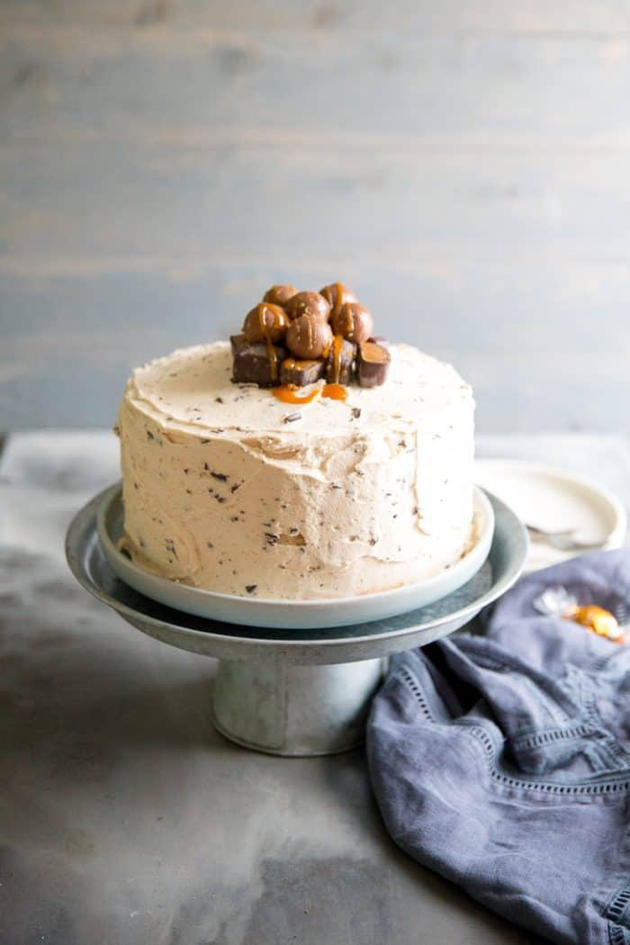 salted caramel chocolate chip cake on a pedestal