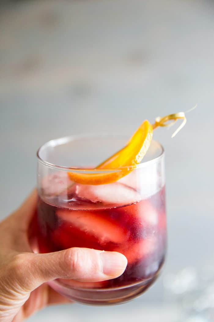 hand holding old fashioned cocktail recipe