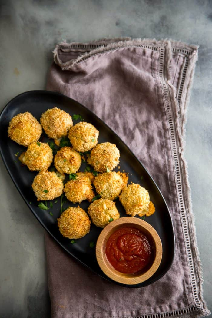risotto balls on a black late with sauce on the side