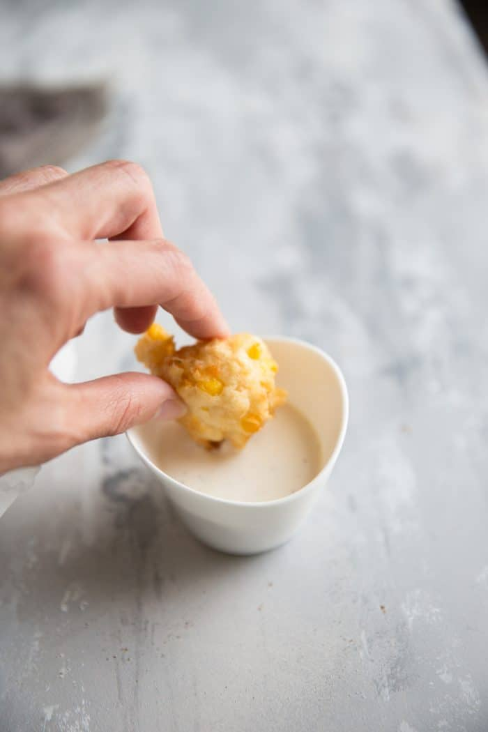 corn fritter being dipped