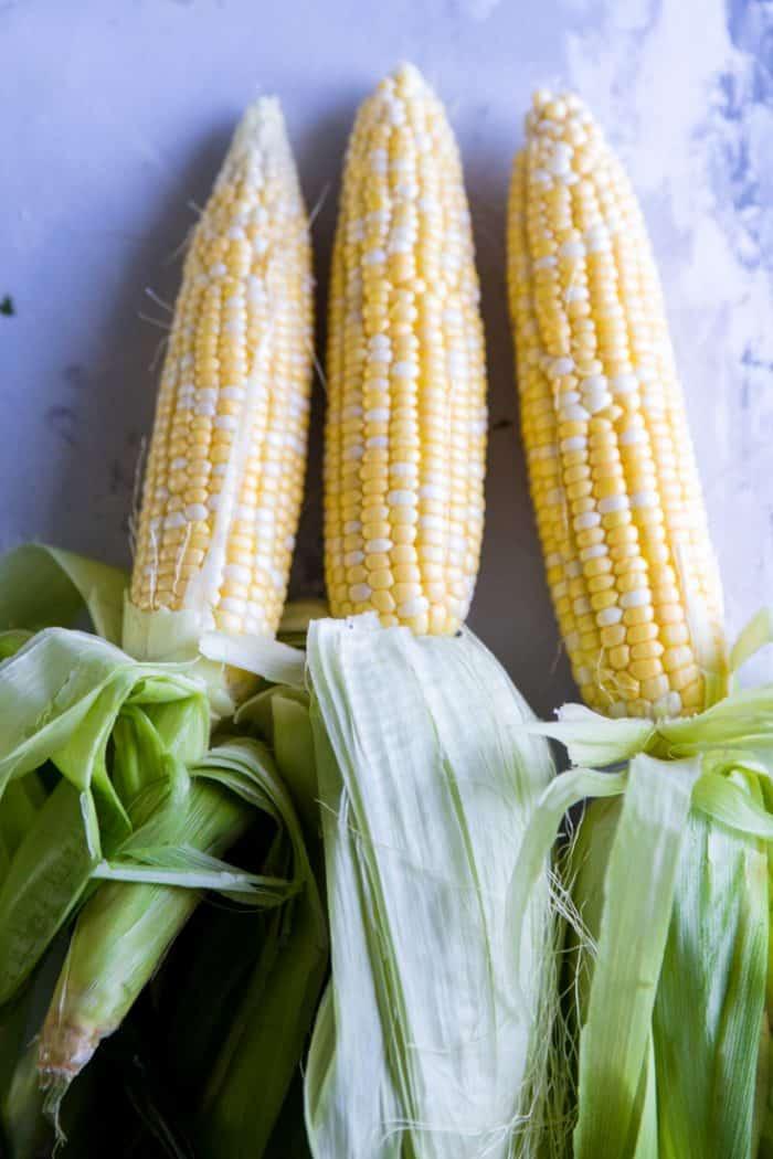 Three uncooked ears of corn