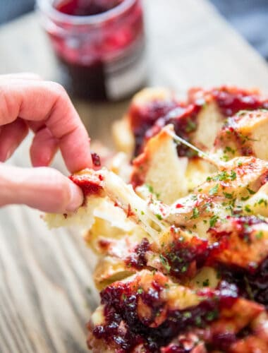 baked brie and jam bread piece being pulled