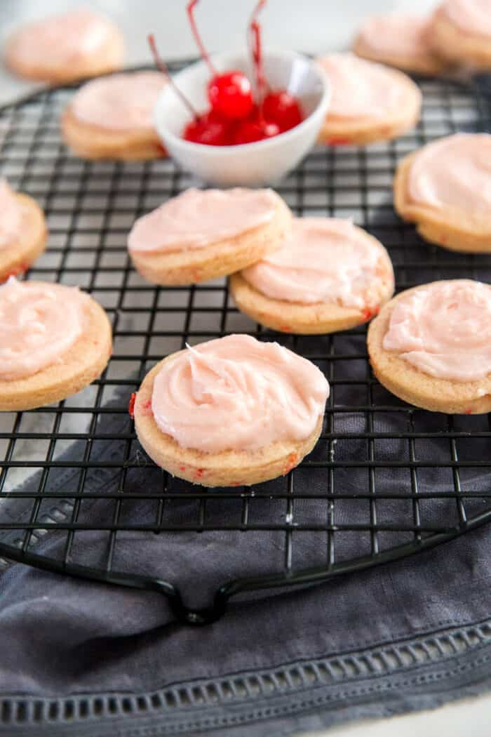 Frosted cherry sugar cookies on a baking rack
