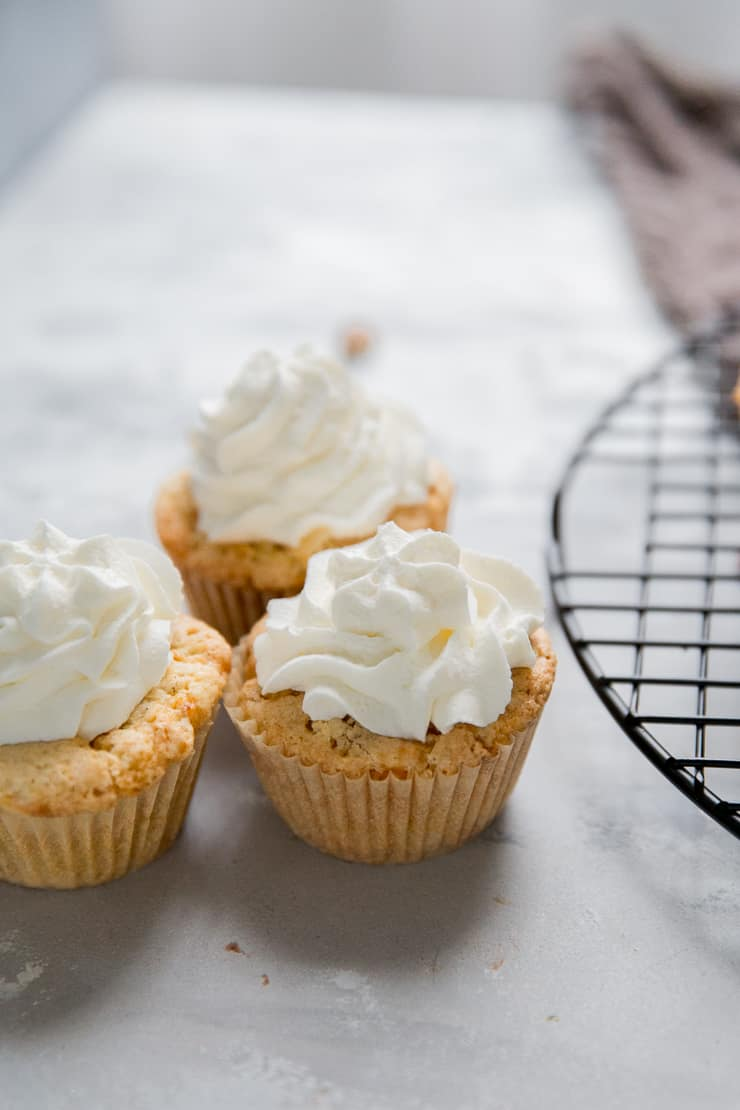 3 carrot cake cupcakes together on a table