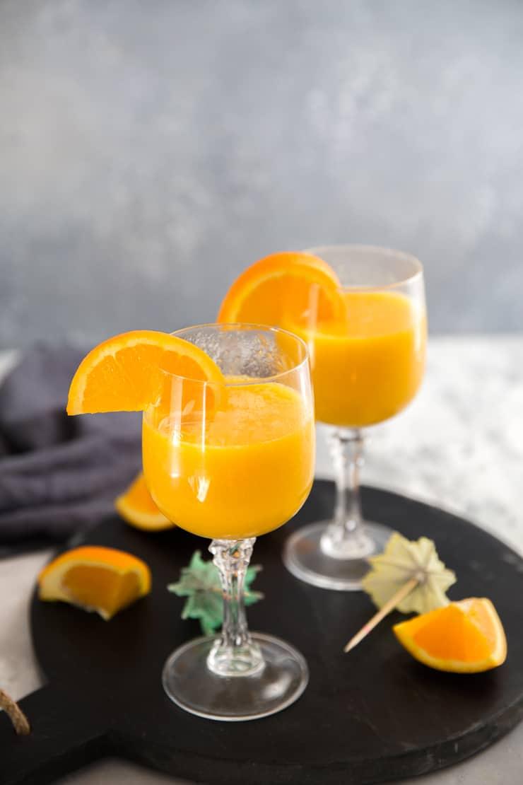 mango mimosa drink on black tray
