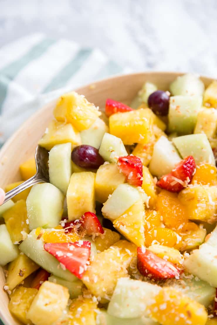 fruit salad with a spoon serving the salad
