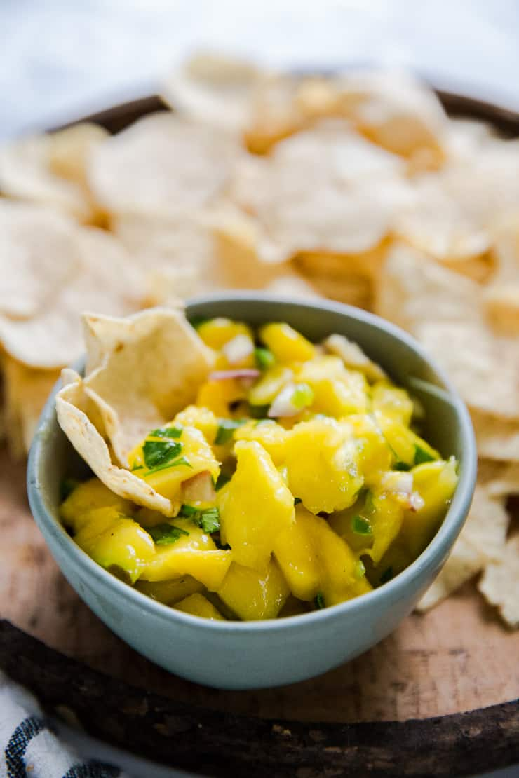 bowl of mango salsa with two chips resting in it