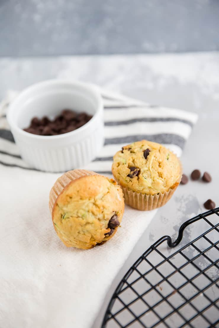 two zucchini muffins next two a bowl of chocolate chips