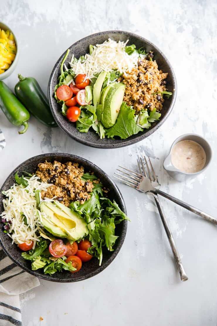 two quinoa bowls on a gray background