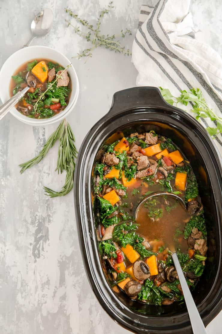 slow cooker with vegetable beef soup and a bowl on the side