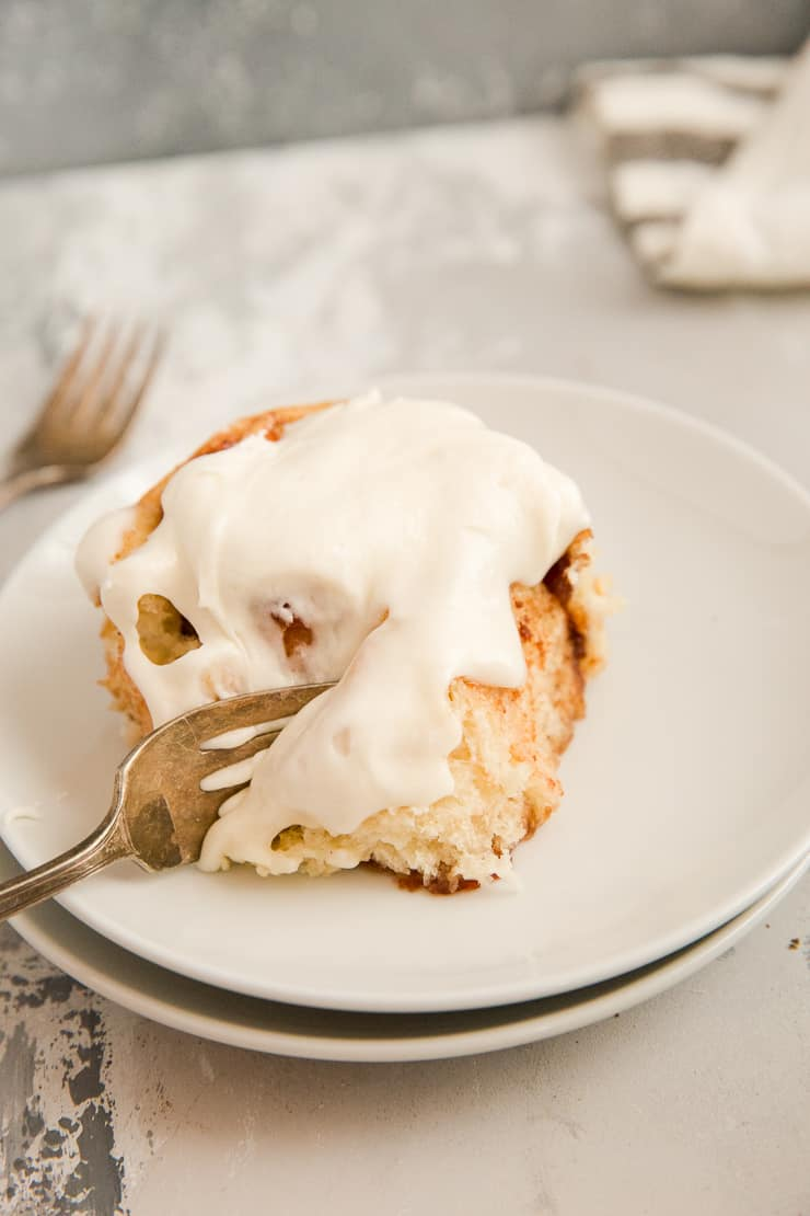 Fork taking a bite out of a cinnamon roll