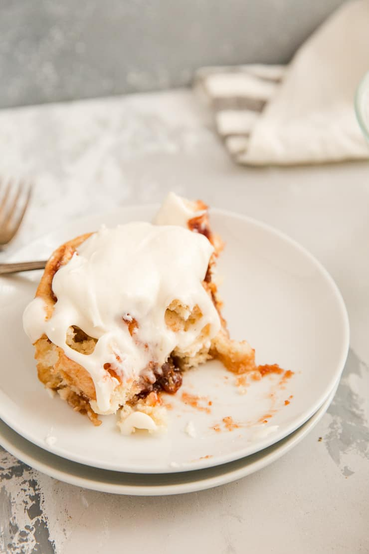 Bitten cinnamon roll on a white plate