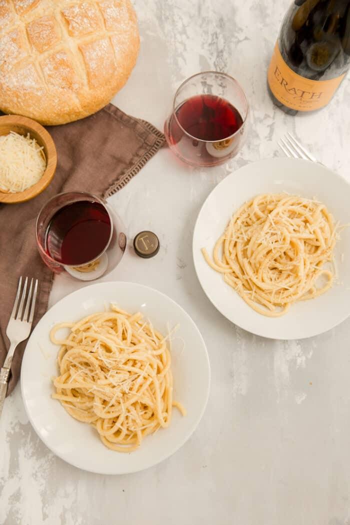 two plates of cacio de pepe with wine