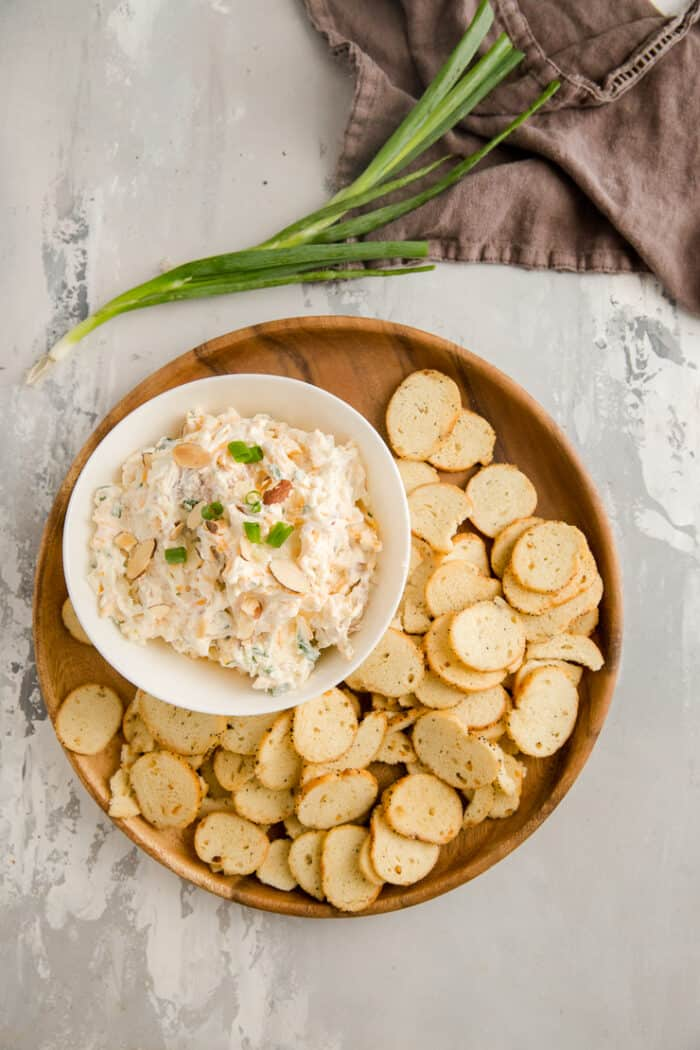 million dollar dip on a brown plate with crackers