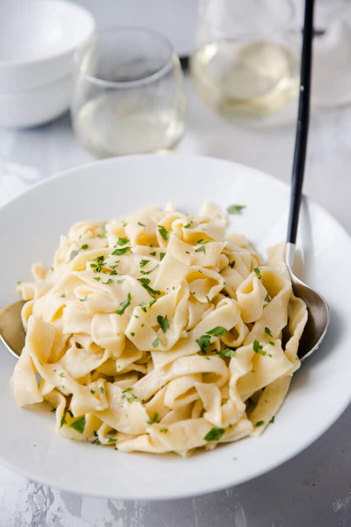 homemade pasta in a bowl with serving utensils
