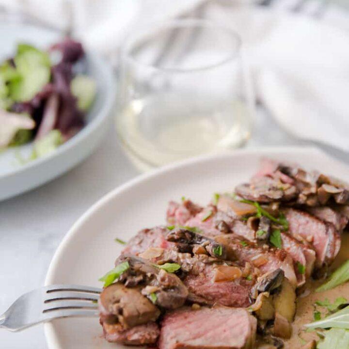 fork taking a bite of steak diane