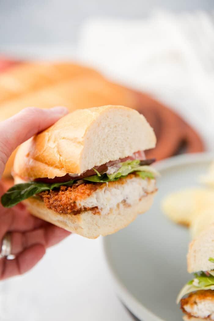 someone holding a catfish sandwich