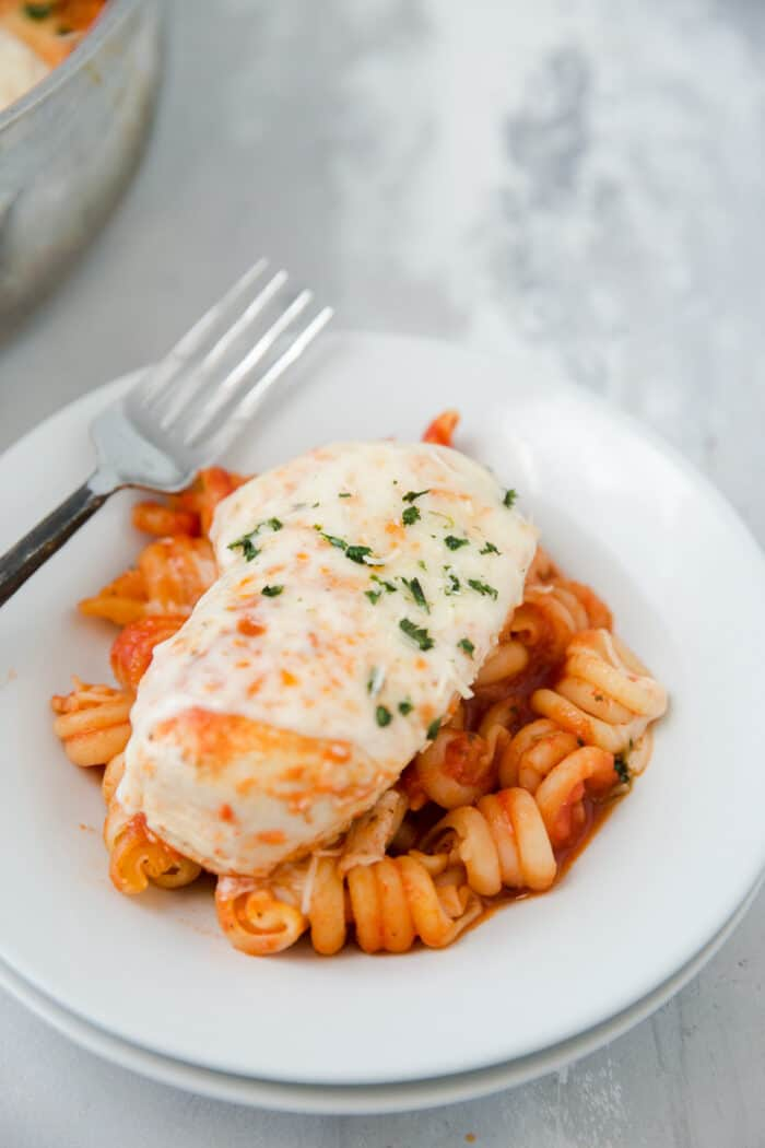 baked chicken parmesan and a bowl of pasta