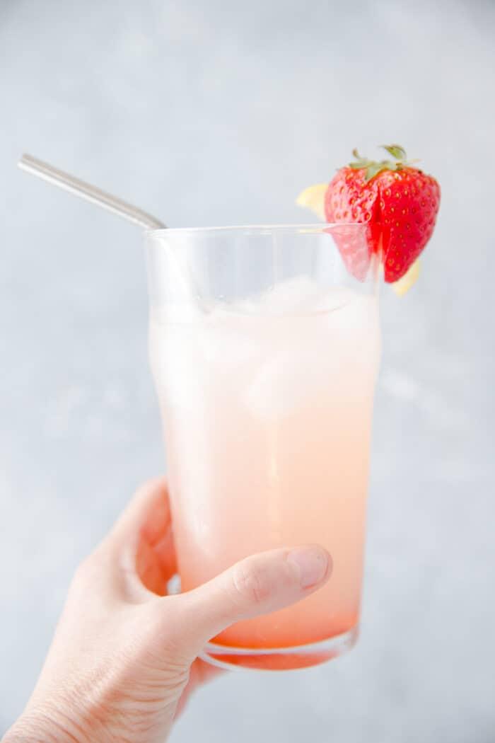 someone holding a glass of vodka lemonade