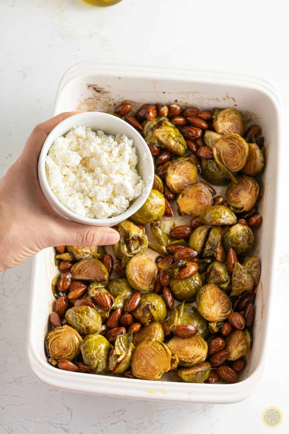 Mixing almonds and the brussels sprouts