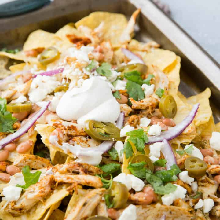 pan of nachos with toppings and white bbq sauce