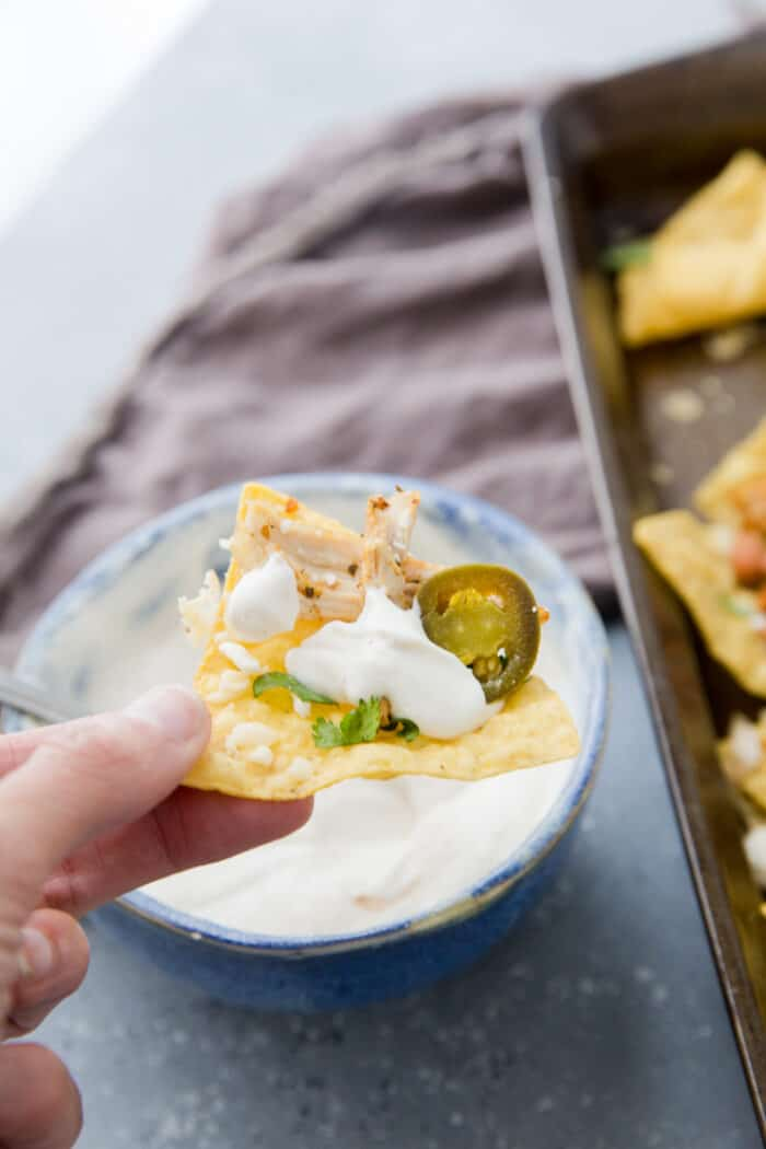 a nacho chip with white bbq sauce on top
